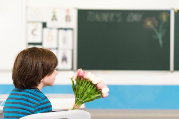 Kind hält einen blumenstrauß für seinen lehrer Kostenlose Fotos