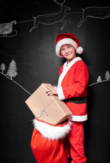 Kind im weihnachtsmannkostümkostüm, das geschenke verpackt Kostenlose Fotos