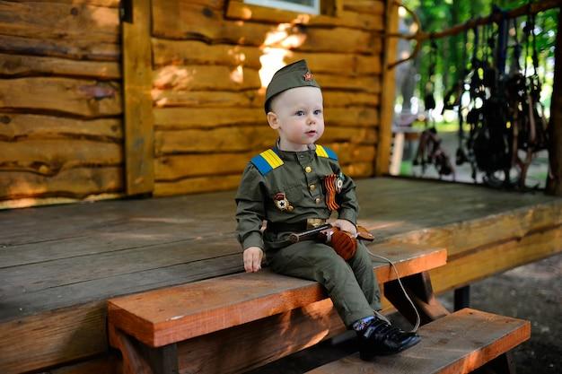 Kind in der militäruniform gegen naturhintergrund Premium Fotos