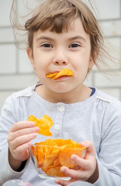 Kind isst chips Premium Fotos