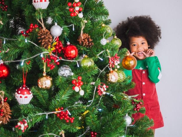 Kind ist glücklich und lustig, weihnachten mit weihnachtsbaum zu feiern Premium Fotos