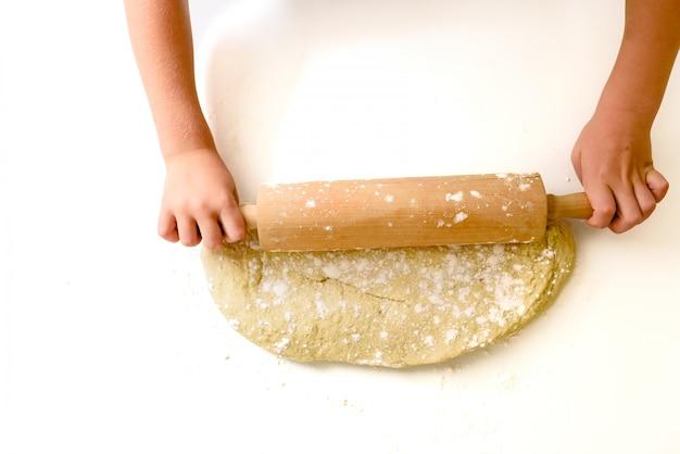 Kind knetet den teig einer pizza, von oben gesehen. Premium Fotos
