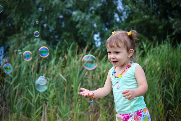 Kind lass die seifenblasen. selektiver fokus Premium Fotos