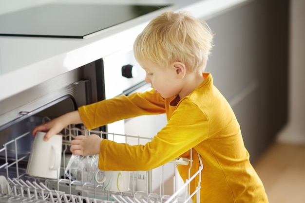 Kind legt schmutziges geschirr in die haushaltsspülmaschine. nahansicht. Premium Fotos