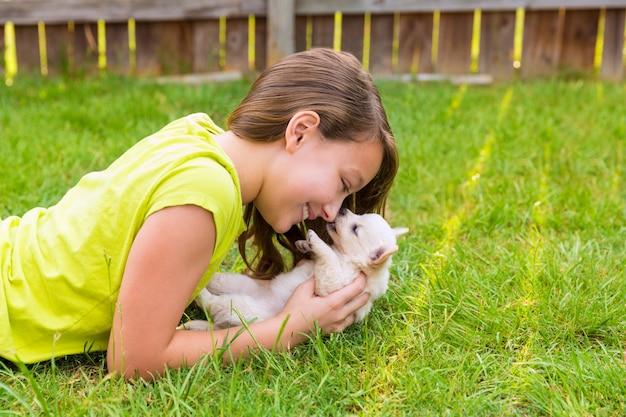 Kind mädchen und welpen hund glücklich im rasen liegen Premium Fotos