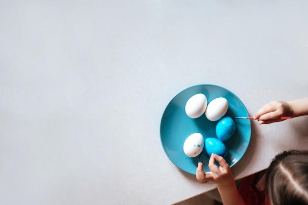 Kind malt ostereier auf blauem teller, der am tisch sitzt nah oben kopienraum Premium Fotos