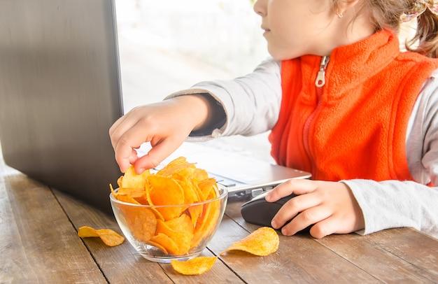 Kind mit chips hinter einem computer Premium Fotos