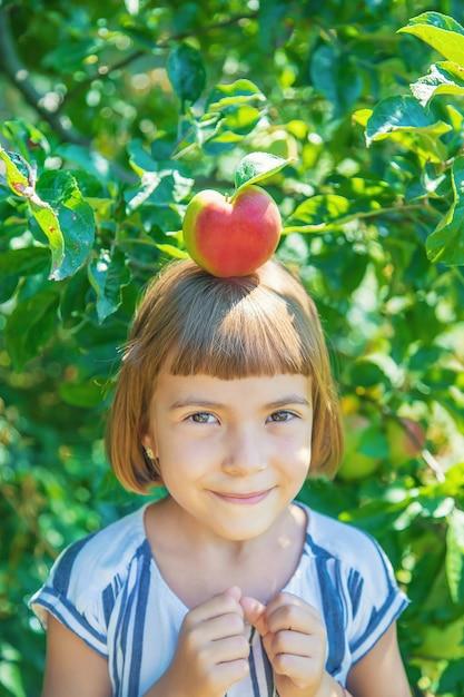 Kind mit einem apfel im garten Premium Fotos