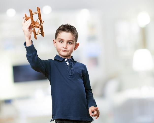 Kind mit einem holz-flugzeug Kostenlose Fotos