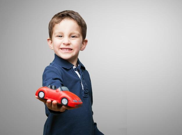Kind mit einem roten auto Kostenlose Fotos