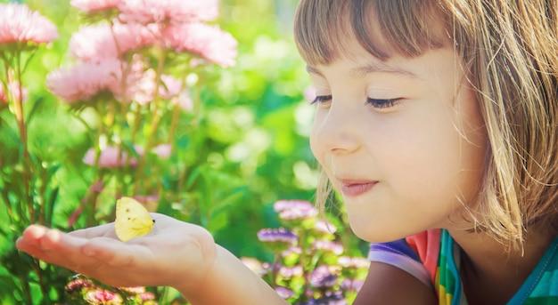 Kind mit einem schmetterling selektiver fokus natur. Premium Fotos