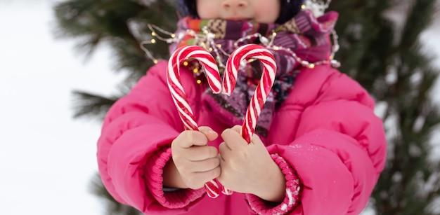Kind mit großen zuckerstangen. weihnachtskonzept. Kostenlose Fotos