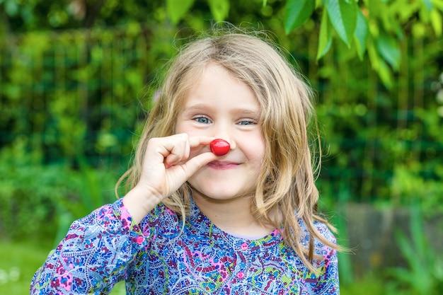 Kind mit kirsche in der hand in einem garten Kostenlose Fotos