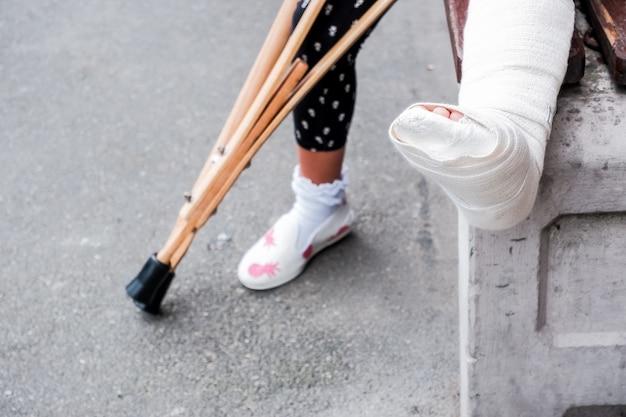 Kind mit krücken und gebrochenen beinen zum gehen, gebrochenes bein, Premium Fotos
