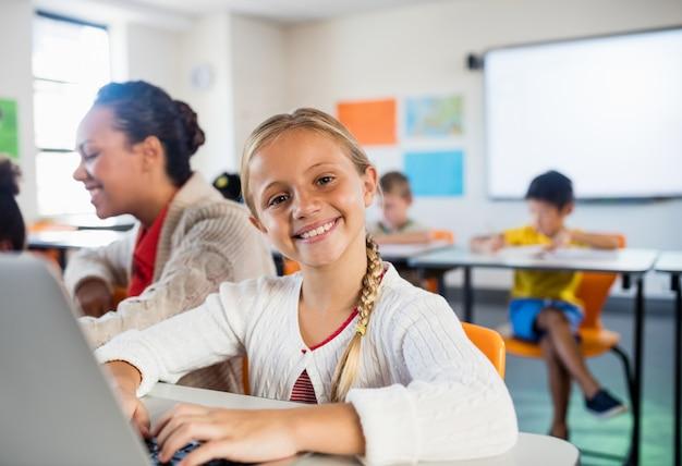 Kind posiert mit ihrem computer Premium Fotos