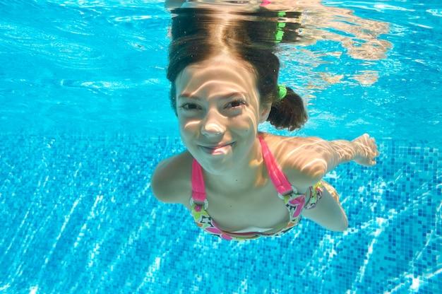 Kind schwimmt im pool unter wasser, glückliches aktives mädchen taucht und hat spaß im wasser, kindereignung und sport auf familienferien Premium Fotos