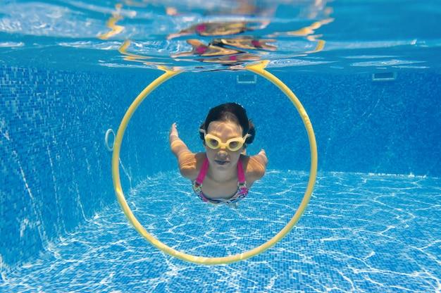 Kind schwimmt im pool unter wasser, glückliches aktives mädchen taucht und hat spaß unter wasser, kindersport im familienurlaub Premium Fotos