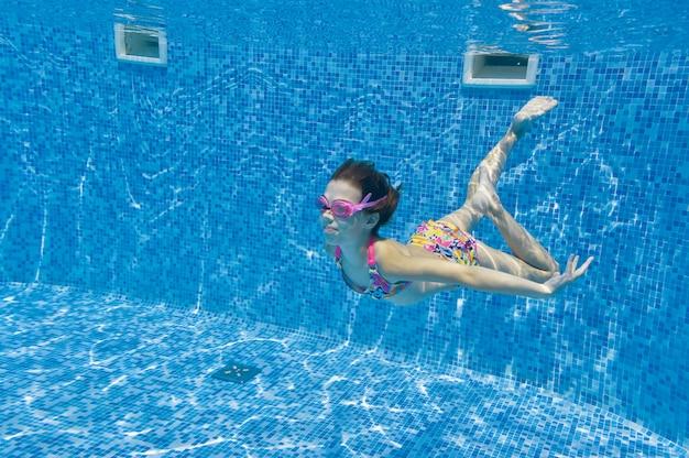Kind schwimmt im pool unter wasser Premium Fotos