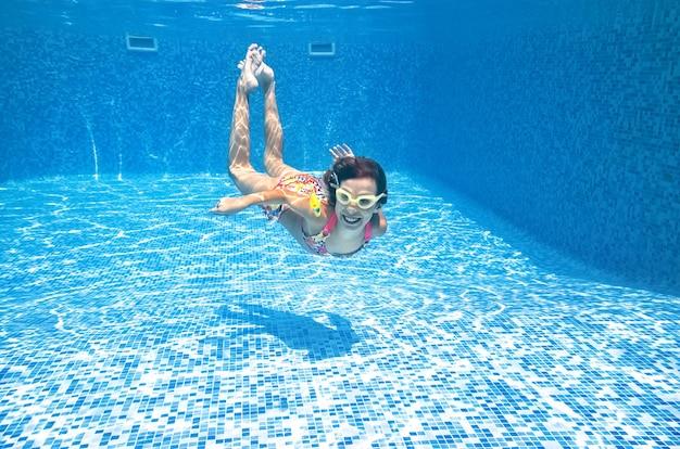 Kind schwimmt unter wasser im schwimmbad, kleines aktives mädchen taucht und hat spaß unter wasser Premium Fotos