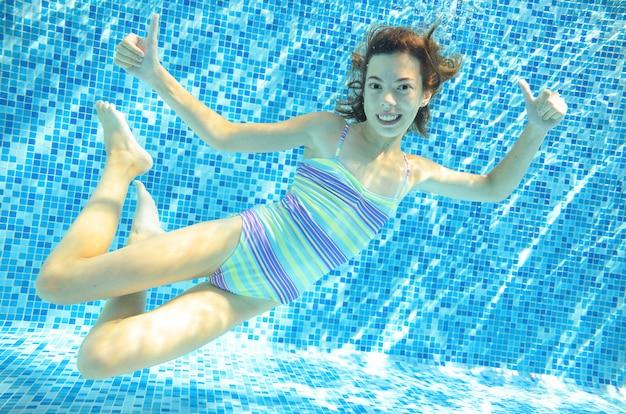 Kind schwimmt unter wasser im swimmingpool, glückliches aktives jugendlichmädchen taucht und hat spaß unter wasser, kindereignung und sport auf familienurlaub auf erholungsort Premium Fotos
