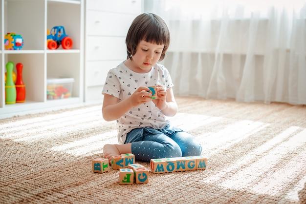 Kind spielt mit holzklötzen mit buchstaben auf gebäude-turm-ausgangskindergarten des bodenraumes des kleinen mädchens. Premium Fotos