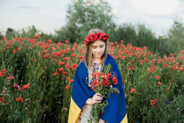 Kind trägt flatternde blaue und gelbe flagge der ukraine im mohnfeld. unabhängigkeitstag der ukraine. flagge tag. Premium Fotos