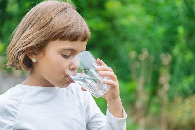 Kind trinkt wasser aus einem glas Premium Fotos