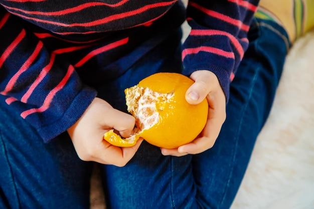 Kind und mandarine. selektiver fokus essen und trinken. Premium Fotos