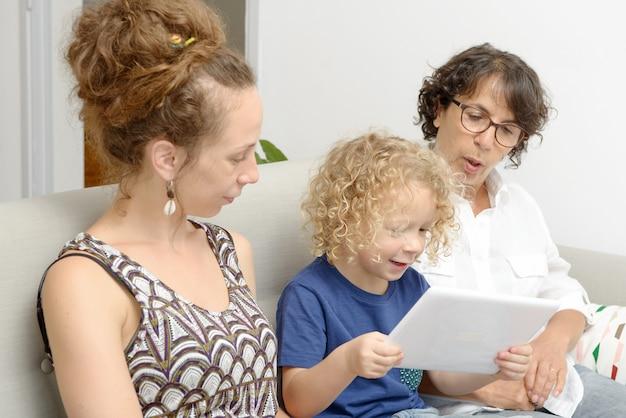 Kind und seine mutter mit großmutter spielen mit tablette Premium Fotos