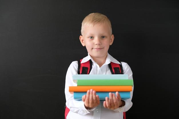 Kind von der grundschule mit büchern und tasche an der tafel Premium Fotos