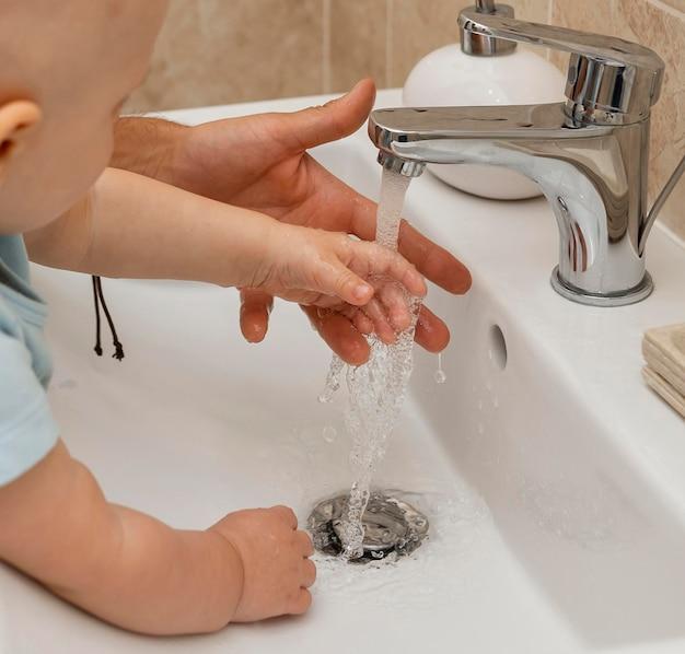 Kind wäscht sich mit hilfe der eltern die hände Kostenlose Fotos