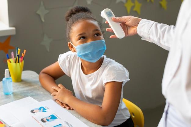 Kind wartet darauf, dass die lehrerin ihre temperatur misst Kostenlose Fotos