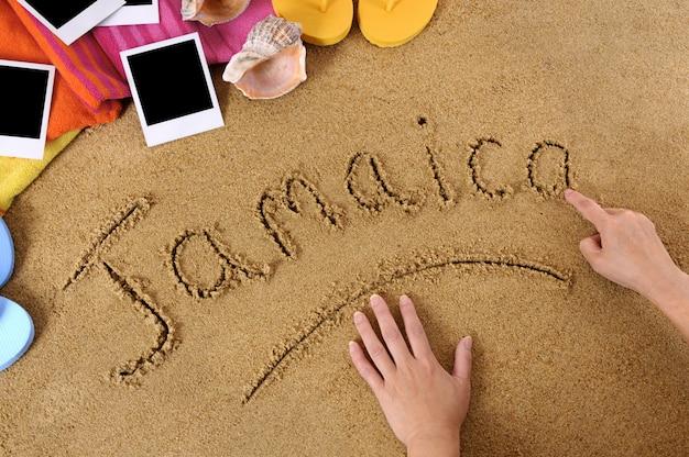 Kind, welches das wort jamaika in sand mit tuch, flipflops und leeren fotodrucken schreibt Premium Fotos