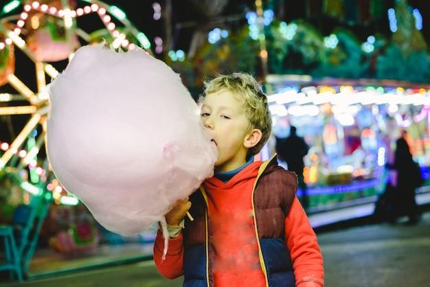 Kind, welches die schöne zeit hat, eine zuckerwatte an einer nachtmesse zu essen. Premium Fotos