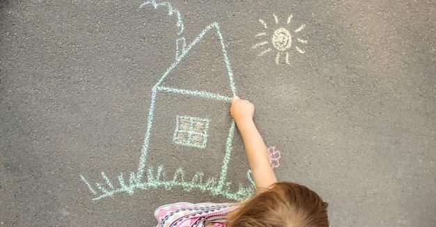 Kind zeichnet ein kreidehaus. selektiver fokus Premium Fotos