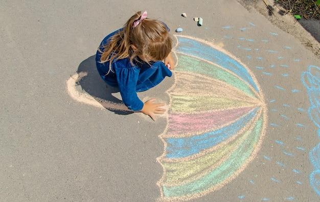 Kind zeichnet mit kreide auf die pflasterung Premium Fotos