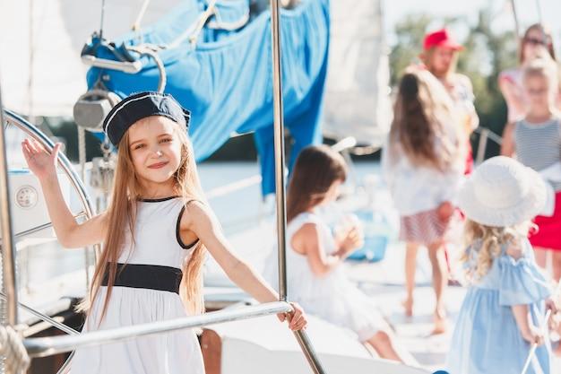 Kinder an bord der seelyacht. teenager oder kind mädchen im freien. farbenfrohe kleider. kindermode, sonnige sommer-, fluss- und ferienkonzepte. Kostenlose Fotos