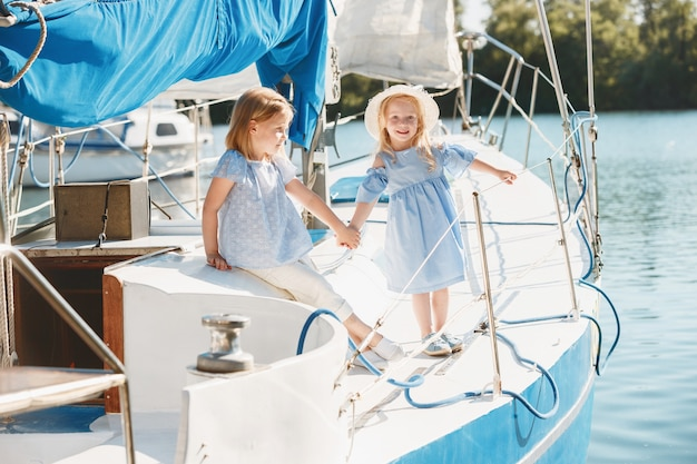 Kinder an bord der seelyacht. teenager oder kind mädchen im freien. farbenfrohe kleider. Kostenlose Fotos