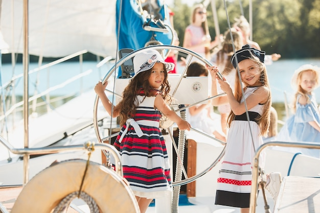 Kinder an bord der yacht trinken orangensaft. teenager- oder kindermädchen gegen blauen himmel im freien. farbenfrohe kleider. kindermode, sonnige sommer-, fluss- und ferienkonzepte. Kostenlose Fotos