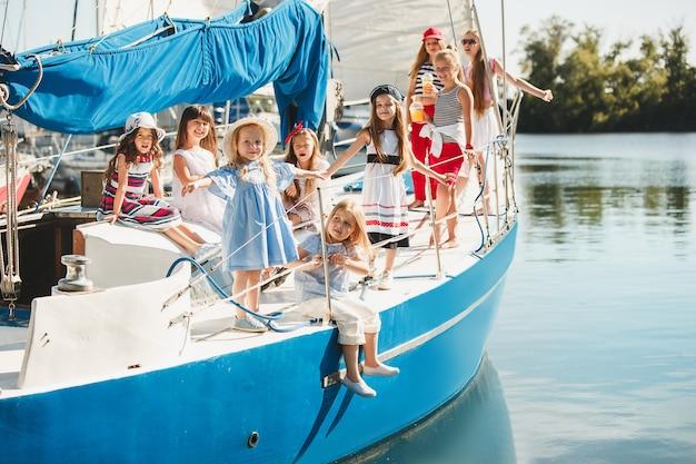 Kinder an bord der yacht trinken orangensaft. teenager- oder kindermädchen gegen blauen himmel im freien. farbenfrohe kleider. Kostenlose Fotos
