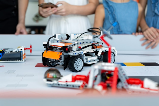 Kinder aus der nähe steuern autoroboter, die aus einem konstruktor zusammengesetzt sind, der auf einem computer in einer robotikschule programmiert ist Premium Fotos
