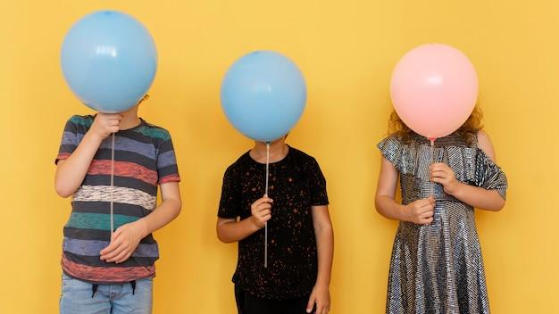 Kinder bedecken gesichter mit luftballons Kostenlose Fotos
