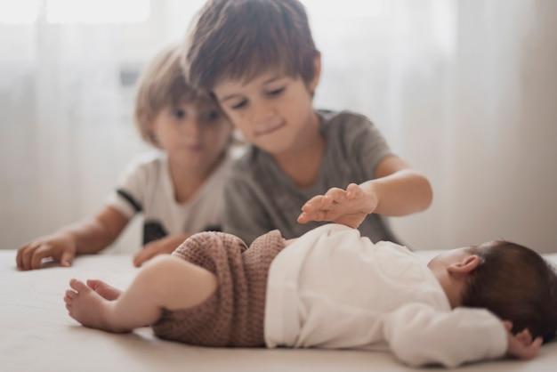 Kinder beobachten ihren kleinen bruder Kostenlose Fotos