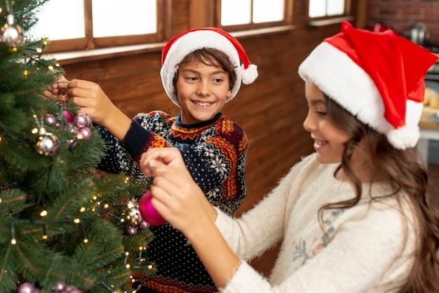 Kinder des hohen winkels, die den weihnachtsbaum verzieren Kostenlose Fotos