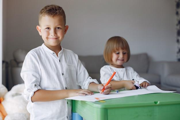 Kinder, die am grünen tisch und am zeichnen stationieren Kostenlose Fotos