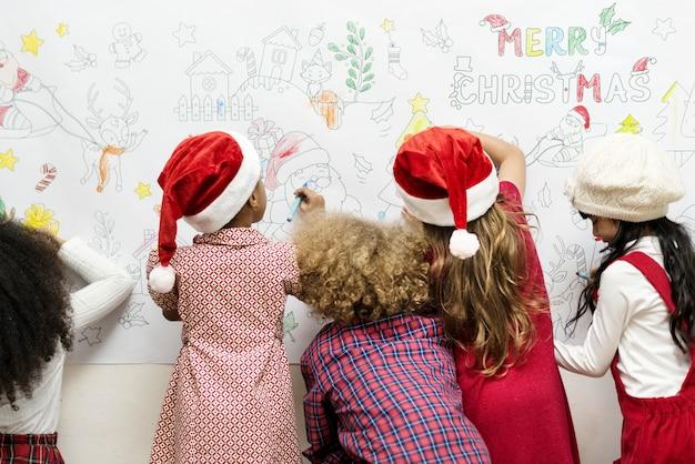 Kinder, die auf eine weihnachtsdekoration zeichnen Premium Fotos