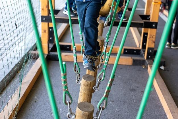 Kinder, die auf stämmen gehen, die an seilen in einem abenteuerpark aufgehängt sind. Premium Fotos