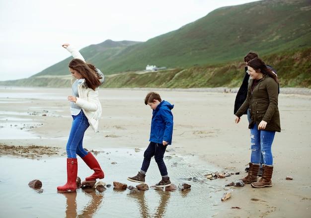 Kinder, die auf steine am strand gehen Premium Fotos
