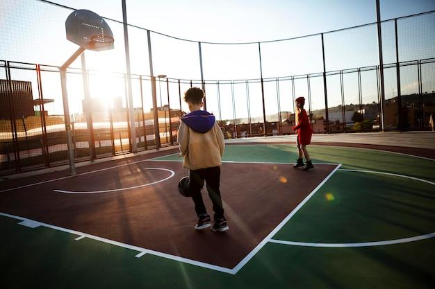Kinder, die basketball auf einem feld spielen Kostenlose Fotos
