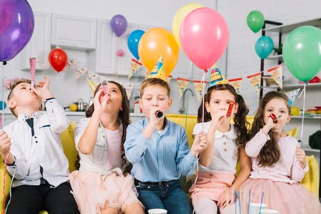 Kinder, die bunte ballone halten und partyhorn während des geburtstags durchbrennen Kostenlose Fotos